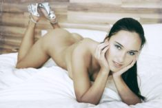 Young beauty in high heels on bed