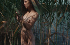 Young nudist beauty by the river in Summer